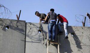 Palästinenser mit einer selbstgebastelten Leiter klttern über die israelische Sicherheitsmauer
