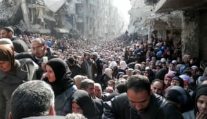 Residents wait to receive food aid distributed by the U.N. Relief and Works Agency (UNRWA) at the besieged al-Yarmouk camp, south of Damascus on January 31, 2014.