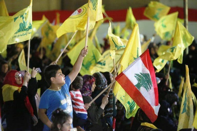 Während einer Rede von Hisbollah-Chef Hassan Nasrallah schwenken Anhänger im Libanon Fahnen der islamistischen Terrororganisation (imago images/Xinhua)