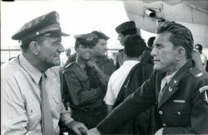 """John Wayne und Kirk Douglas 1965 bei den Dreharbeiten für den Film """"Cast A Giant Shadow"""" (dt.: """"Der Schatten des Giganten""""), einen der bekanntesten Filme über den israelischen Unabhängigkeitskrieg. (imago images/ZUMA/Keystone)"""