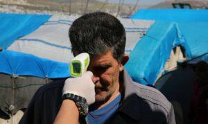 Mitarbeiter einer NGO misst in einem Flüchtlingslager in Idlib Fieber