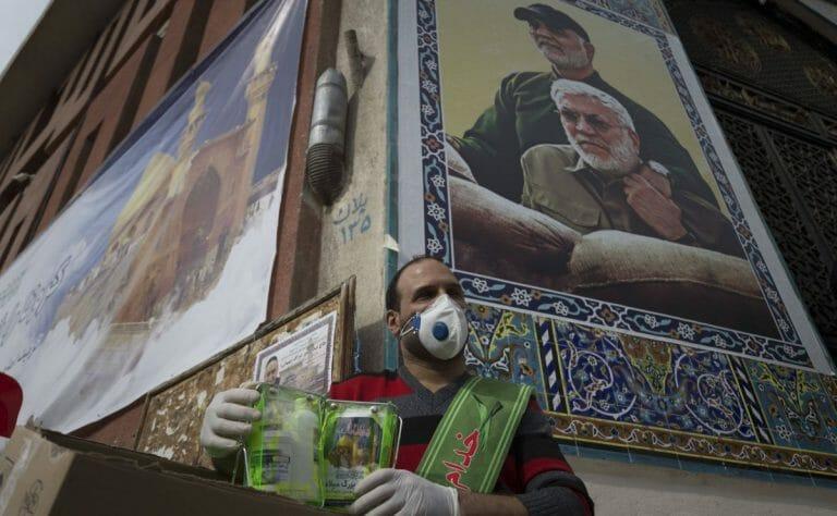 Helfer im Iran, der Autos wegen des Coronavirus desinfiziert
