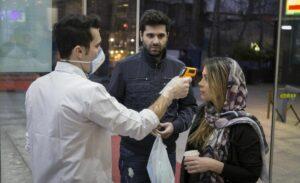 Mitarbeiter eines Einkaufszentrums in Teheran misst bei Kunden Fieber