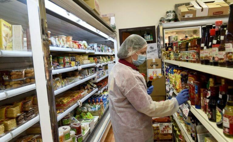 Mitarbeiterin eines israelischen Supermarktes trägt Corona-Schutzkleidung