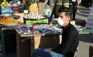 Verkäufer auf Markt in Bagdad mit Corona-Maske