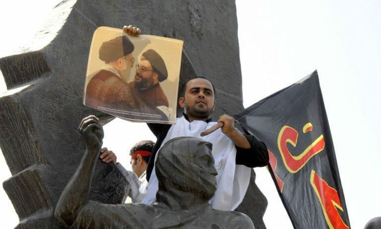 Demonstrant hält Plakat mit Irans oberstem Führer Khamenei und Hisbollah-Chef Nasrallah hoch