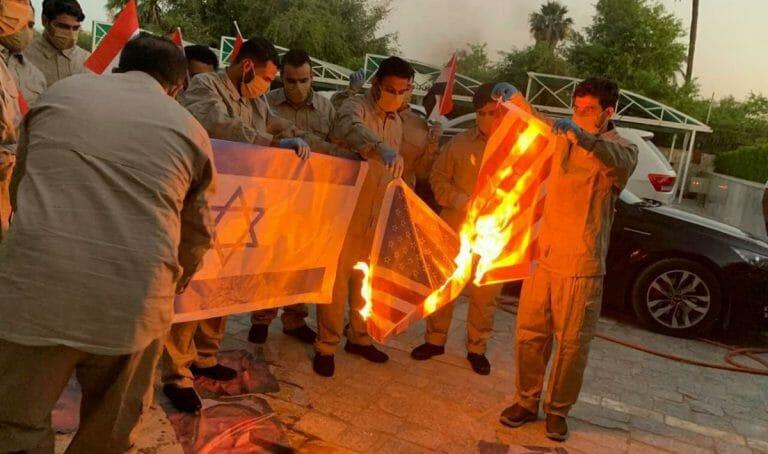 Mitglieder der pro-iranischen schiitschen Hisbollah-Kataib-Miliz zertrampeln Bilder des irakischen Premierministers und verbrennen Flaggen