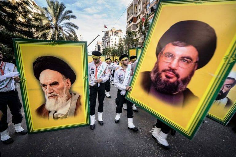 Hisbollah-Anhänger im Libanon mit Plakaten von Hisbollah-Chef Nasrallah (rechts) und Khomeini. (imago images/ZUMA Press)