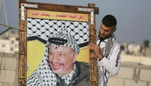 """Jugendlicher mit Arafat-Poster anlässlich des 56. Jahrestags der Gründung des """"Fatah Youth Movement"""""""