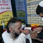 """Mitarbeiter des israelischen """"Roten Davidstern"""" impft einen Palästinenser am Qalandiya-Grenzübergang"""