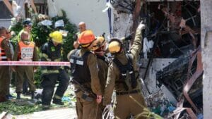 Israelische Rettungskräfte vor einem von einer Hamas-Rakete getroffenen Wohnhaus