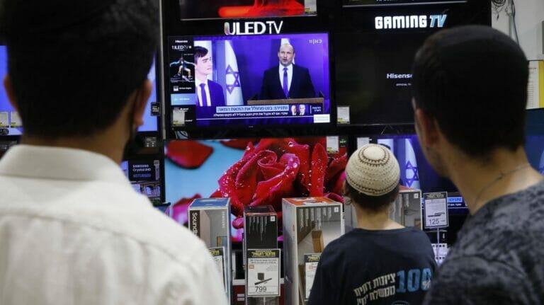 Israelis sehen die Pressekonferenz auf der Naftali Bennett seine Einigung mit Yair Lapid bekannt gibt