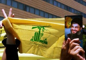 Flagge der Hisbollah, Bild von Hisbollah-Gegeneralsekretär Hassan Nasrallah. (© imago images/UPI Photo)