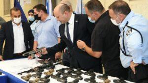 """Premier Bennet betrachtet im Rahmen der """"Operation Sword Strike"""" konfiszierte Waffen"""