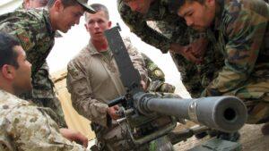 Ausbildner der US Marines schult afghanische Soldaten an einem Machinengewehr